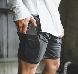 venda por atacado 2019 New Men Ginásio de Esportes de compressão de telefone de bolso camada de desgaste Em Base calças curtas Atlético Sólidos calças justas Shorts Calças