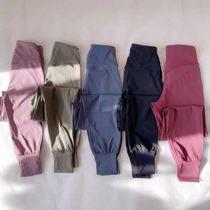 Голые чувствующие ткани свободные подходят спортивные йоги брюки тренировки бегуны женщин масло мягкий эластичный тренировочный тренажерный зал пробежки с двумя боковыми карманами
