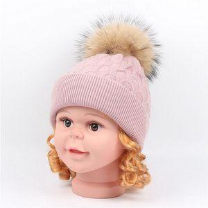 Sombrero de punto de pelo de conejo de alta calidad para niños bebé mapache bola de piel de color sólido que se encrespa casquillo de la cabeza sombrero de protección de oído caliente sombreros de invierno 1-6T