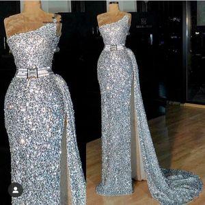 Silber Sequined Hüllen-Abschlussball-Kleid mit Schärpe eine Schulter Modest Side Split Abendkleid billig spezielle Gelegenheits-Kleid-Partei-Abnutzung