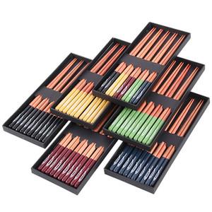 Los nuevos palillos de madera japoneses situados a 5 pares de palillos puntiagudos usados comúnmente en uso en el hogar y una caja de 23cm de la cena los palillos T3I5039