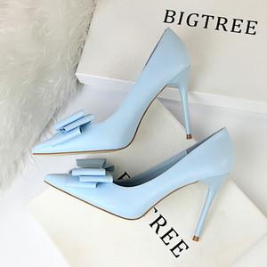 Dünne, High Heels machen Frauen die Schuhe mit einem bonbonfarbenen Bogen