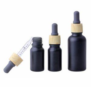 بيع أعلى 10ML 30ML أسود لامع الأساسية مصل النفط وقوارير زجاجية قطارة للتغليف مستحضرات التجميل مع أنبوب غطاء الخيزران البلاستيك
