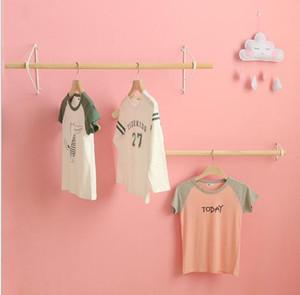 Grucce per vestiti in negozi di abbigliamento per bambini Espositore di moda appeso a parete Negozio di abbigliamento Appendiabiti Negozio di abbigliamento per bambini
