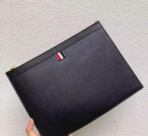 New unisex clutch. Ribbon-decorated fashion casual clutch, made of grain-grain leather. Striped lining, zip closure switch.
