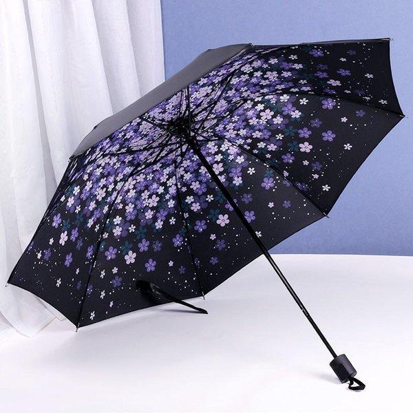 Pequeño paraguas negro con cereza púrpura.