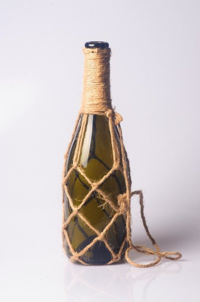 Handgemachter Dekorationsbehang brauner Glasflaschenvasenbecher-Glaskrug mit Grasstroh