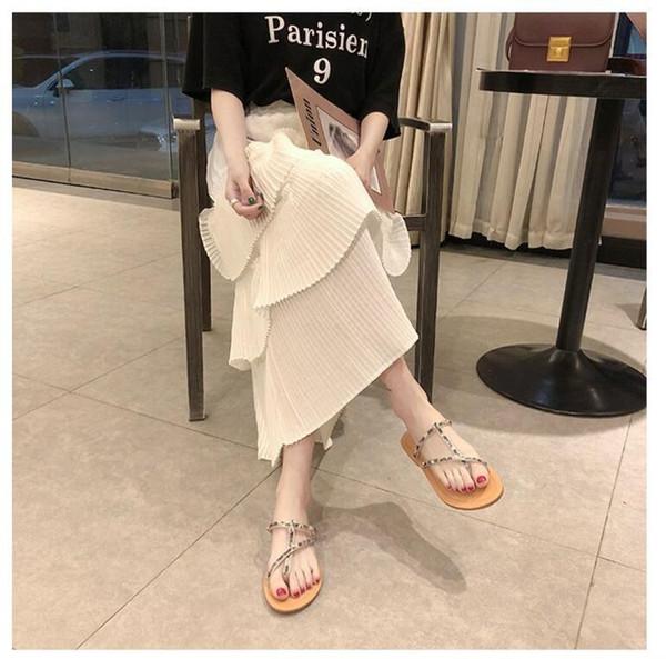 Les femmes qui portent des sandales à la mode 2019 portent des sandales à tongs à fond plat et des sandales en forme de diamant à base d'eau pour la mode décontractée