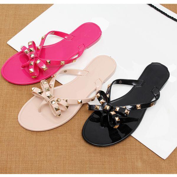 2019 moda kadın sandalet düz jöle ayakkabı yay V çevirme damızlık plaj ayakkabı yaz perçinler terlik Tanga sandalet çıplak