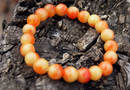 Asian Carved Beads Canada - Hand-carved Yuanzhu. Red and yellow jade bracelet. 10 mm, 21 beads strung with rubber bands.