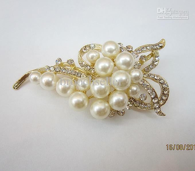 Perla de oro bañado en crema y broche de diamantes de imitación con forma de arco de novia.